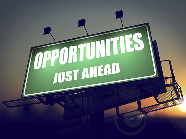 The words, Opportunities Just Ahead, are on a green billboard with the sunrise behind it.