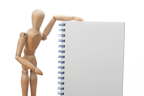 A wooden Manikin figure gesturing toward a blank spiral notebook