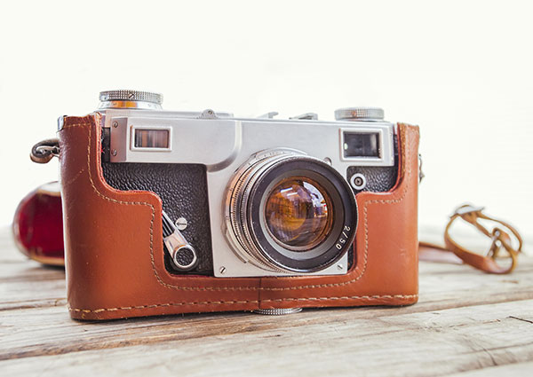Vintage camera in an orange case on wooden table