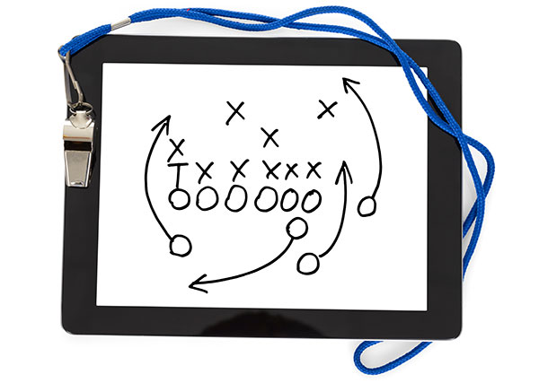 A whistle lays on top of a digital tablet that is displaying a football strategy play.