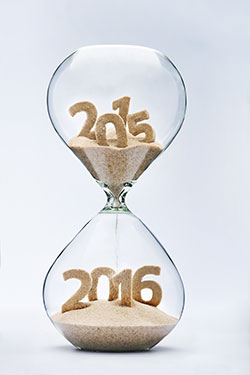 A 2016 New Year concept: an hourglass with sands of 2015 flowing into the bottom chamber for 2016.