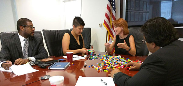 Small Business Administration executives collaborate with using LEGOs during a meeting.