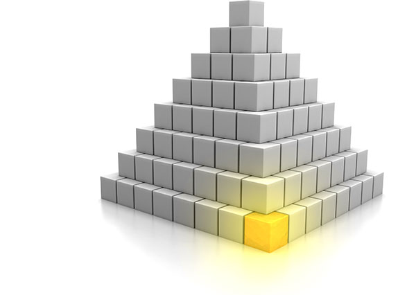 Cornerstone concept of a pyramid of cubes; all are gray except one foundation corner cube that glows in gold