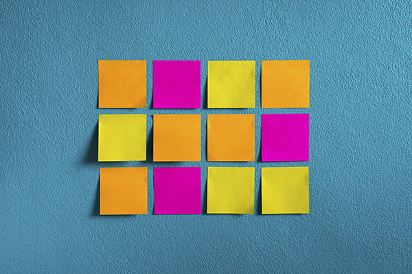 Three rows of different colored paper sticky notes on a wall.