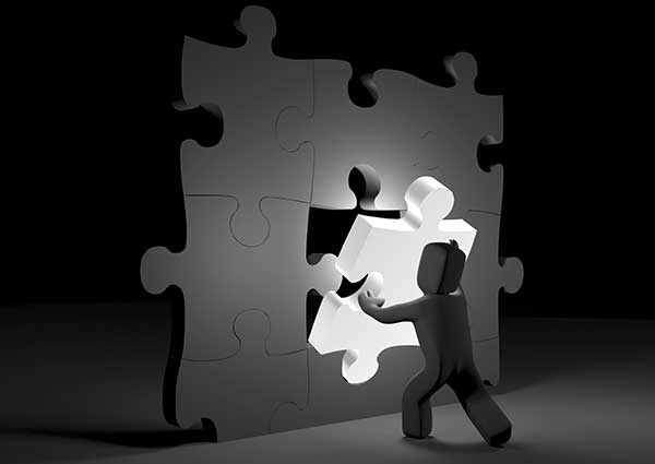 A figure in a dark room adds an important puzzle piece that is illuminated to a wall of white puzzle pieces.