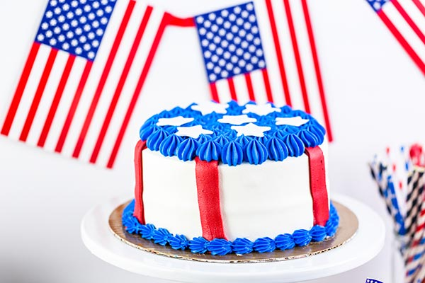 A red, white, and blue cake with American flags in the background.