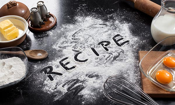 The word recipe is written into flour on a table, surrounded by baking ingredients and utensils.