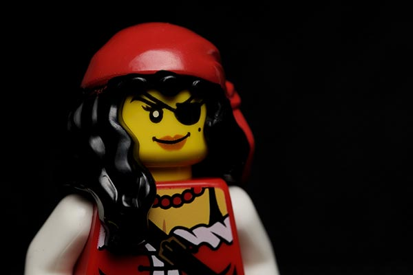 A colorful lady pirate LEGO toy against a black background