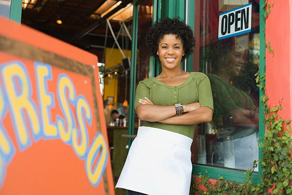 Female small business owner standing in front of her open coffee shop