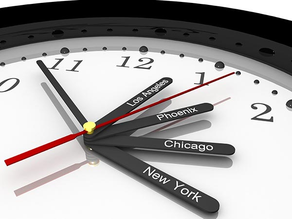 A clock with multiple hands that have U.S. cities on them