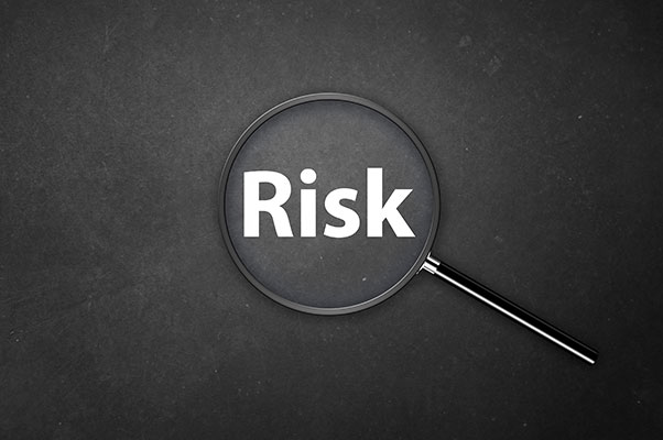 The word risk is in white text on a dark blackboard, with a magnifying glass over the word.