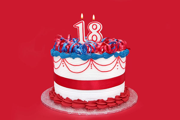 A red, white, and blue celebration cake with two lit candles, a one and an eight, for the number 18.