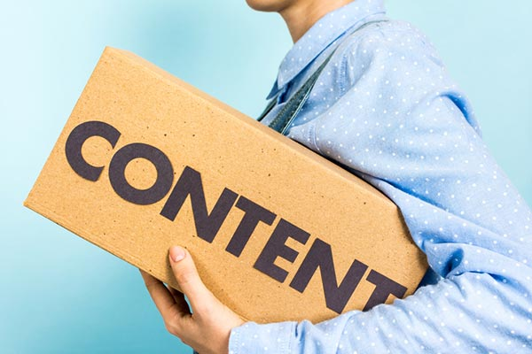 Woman carrying a box with word Content on it; a content marketing distribution concept.