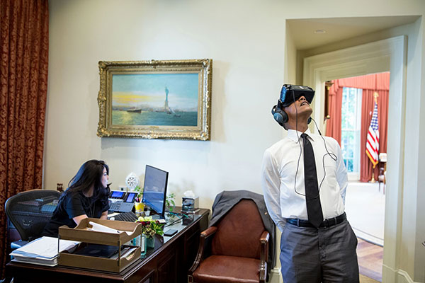 President Barack Obama uses a virtual reality headset in the Outer Oval Office, Aug. 24, 2016. Personal aide Ferial Govashiri sits at her desk at left.