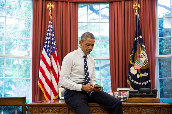 President Obama looks at a mobile device in the Oval Office.