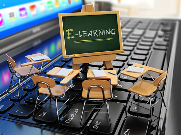 E-learning-concept of miniature school desks and chalkboard on a laptop keyboard.
