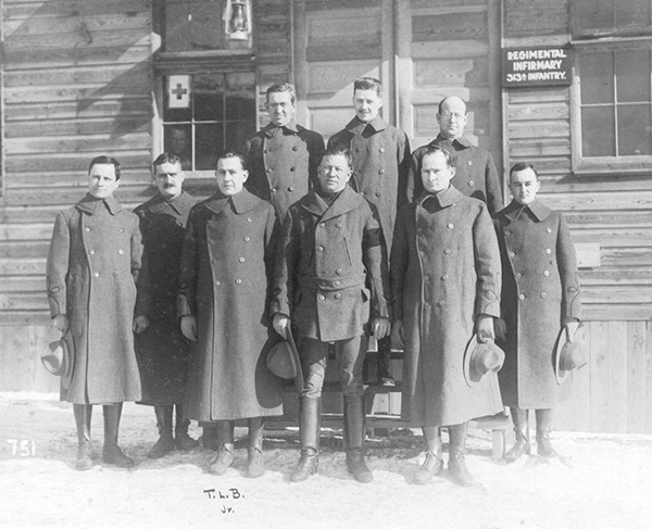 Captain Timothy Barber stands with members of the 313th Infantry Regiment.