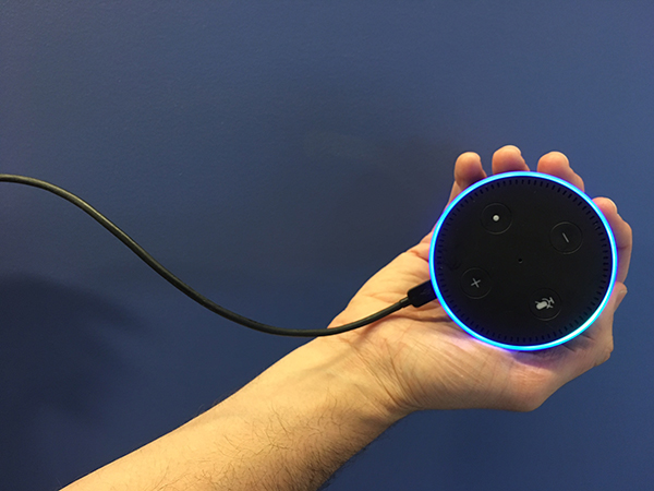 A hand holding the Amazon Echo Dot (Alexa).