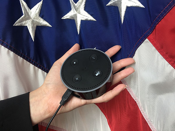 A hand holds an Echo Dot from Amazon in front of an American flag.