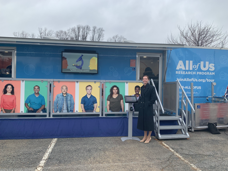 Adele is smiling as she stands outside a trailer that is covered in posters featuring a diverse group of individuals. On the trailer, a sign reads, All of Us Research Program.
