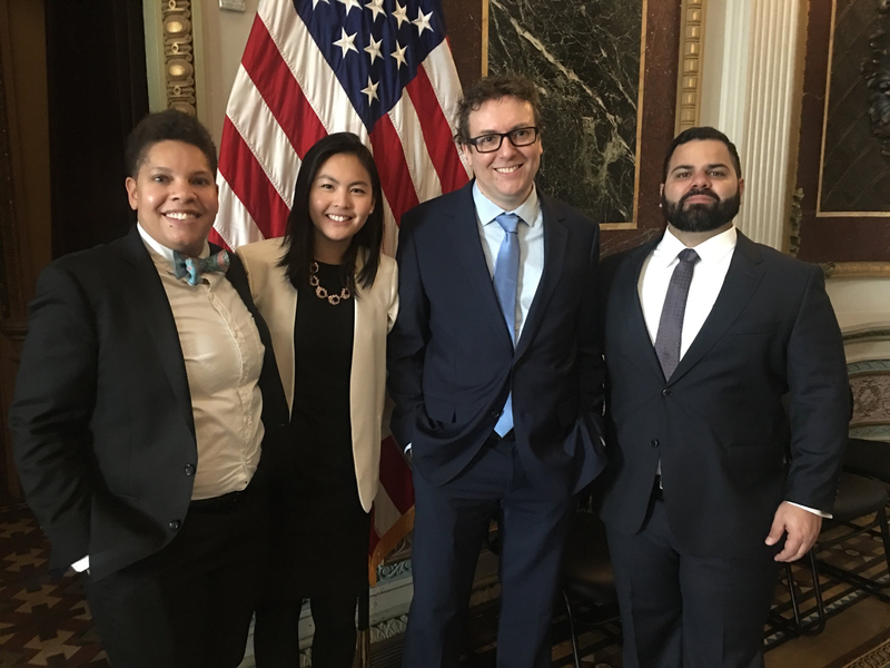Clarice stands in front of a United States flag with three other Presidential Innovation Fellows. All are smiling and wearing professional-formal attire.