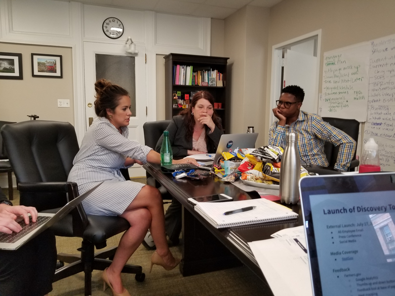 An intimate working session in a conference room where two USDA Apprentices (seated center, and right) are collaborating on a project with a GSA employee (seated on the left).