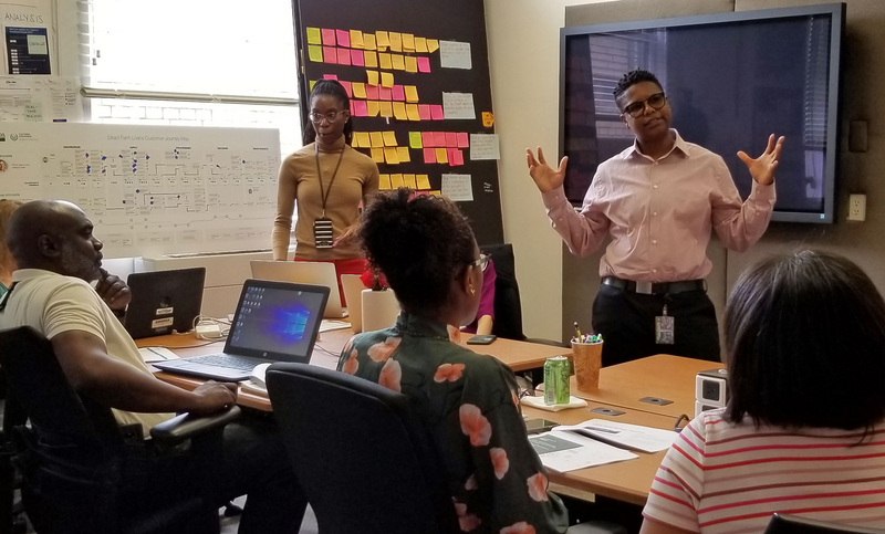A photo of a USDA Apprentice leading a human-centered design workshop. Three people are working at a table on an activity, and one person is standing in front of a customer journey map and a tall, dark board with colorful sticky notes of ideas from a brainstorming session.
