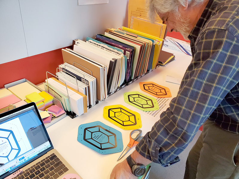 An employee reviews four ideas printed on blue, yellow, green, and orange paper gem icons.