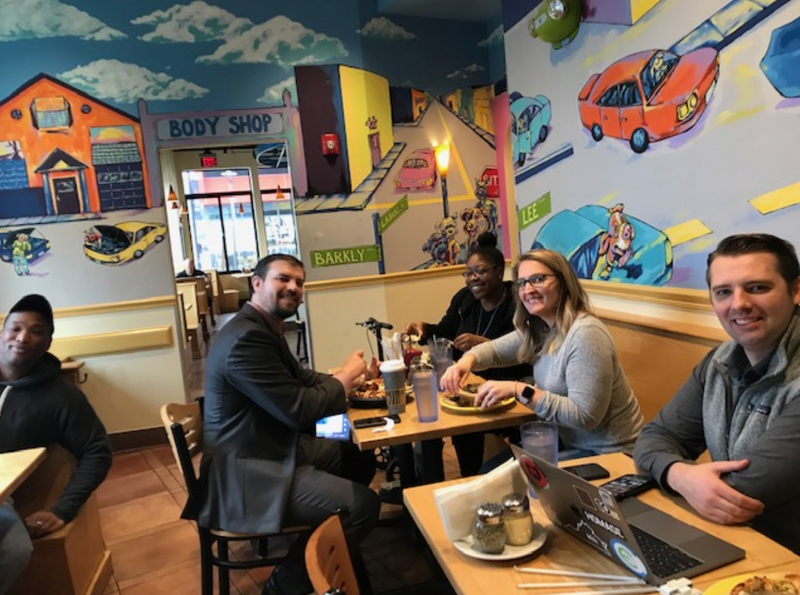 Five employees have a working lunch at a restaurant in Virginia.