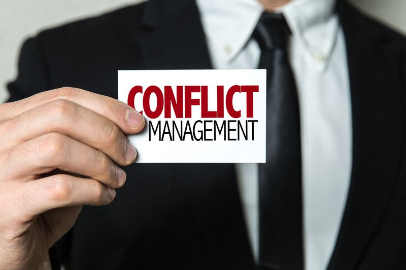 A close-up on a business man holding a small sign that reads, Conflict Management.
