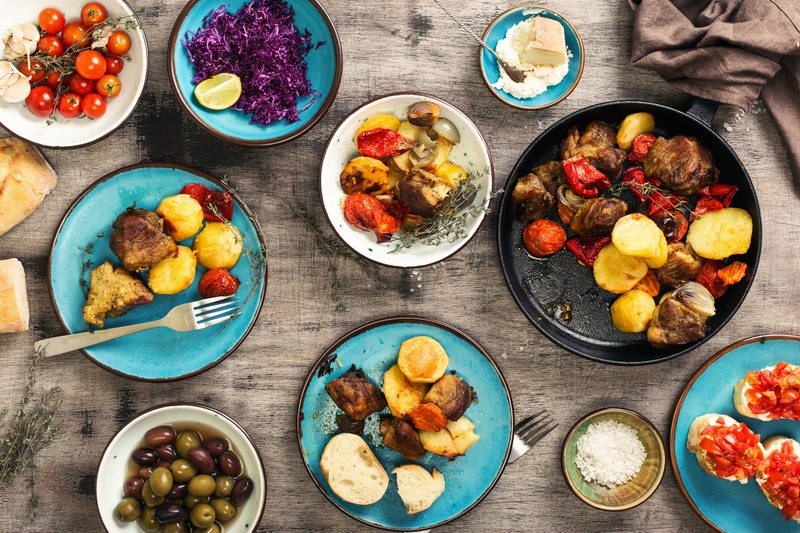 A photograph of a dinner table with plates, bowls and utensils. The dishes are holding olives, salt, bruschetta, tomatoes, cabbage, and bread, and there is a frying pan with potatoes and meat.