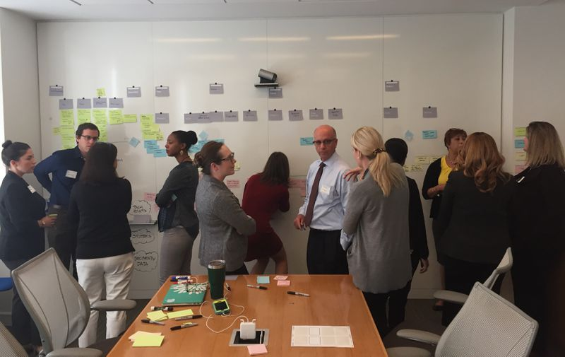 A team from each agency works on a journey map exercise at the board.
