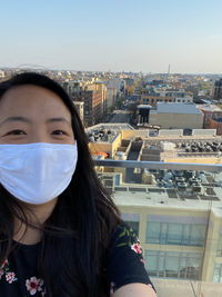 Kaeli stands outside in Washington, DC. She wears a floral shirt and a white mask to protect herself from COVID-19. It is a sunny, blue-sky day, and behind her you can see city buildings and the DC skyline, including the Washington Monument.