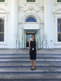 Dr. Kaeli Yuen stands smiling outdoors. She is on the steps of a government building.