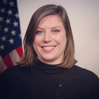 Photo of Kelly Confer with the American flag and a white wall behind her. She is smiling and wearing a black turtleneck and sweater.