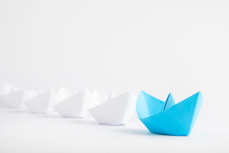 Leadership concept, represented by a blue paper ship leading a row of white paper ships
