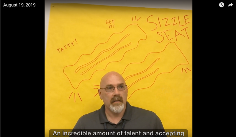 Screen capture of a video player and one man speaking in front of a bright yellow backdrop. Caption: Internal storytelling videos, like The Sizzle Seat, lift up employee stories.