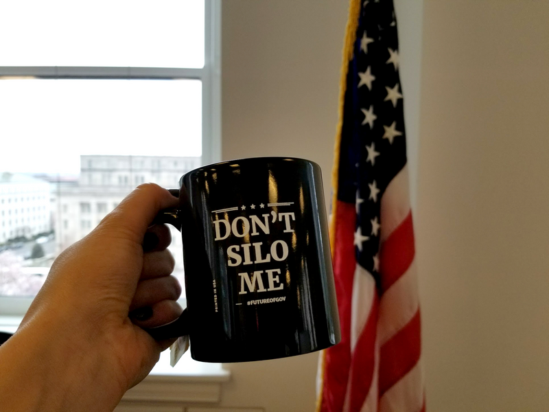 Photo of a hand holding up a black coffee mug that has the words, Don't Silo Me, and the hashtag, Future Of Gov, in white lettering; in the background is an American flag near an office window.