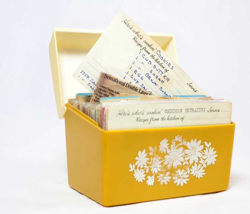A photograph of an open recipe box, with recipes written on index cards in it.