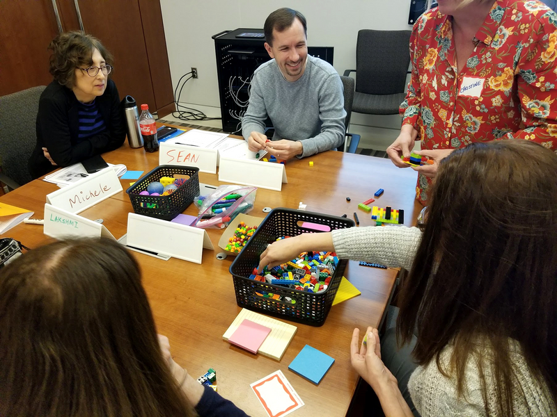 This photo shows a close up of a group of people working together in a collaboration workshop around a small, shared table. The purpose of the workshop is to solve government problems by using human-centered design. There are five people in the photo, two are facing the camera. All of the people are sitting around a table that has colorful building block toys and Post-It notes. The people that are facing the camera are engaged and look happy.