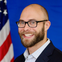 Photo of Tim Lowden. He is smiling, wearing dark rimmed glasses, dark suit jacket, and white shirt, standing in front of a blue wall and the American flag.