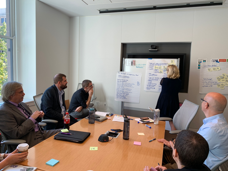 Photo of a people working together in a conference room at GSA. All are seated at tables while one person takes notes at a whiteboard.