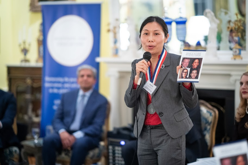 Wanmei Ou stands inside an ornate room at a speaking event on artificial intelligence. She is speaking into a microphone and holds a photo of four faces. She wears a grey suit and a red shirt.