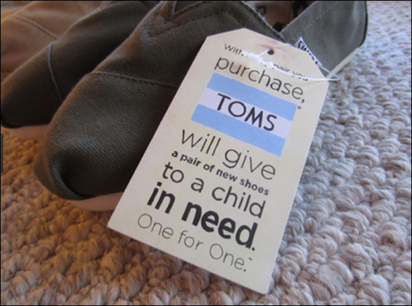 A pair of TOMS shoes with their pledge to donate to a child in need