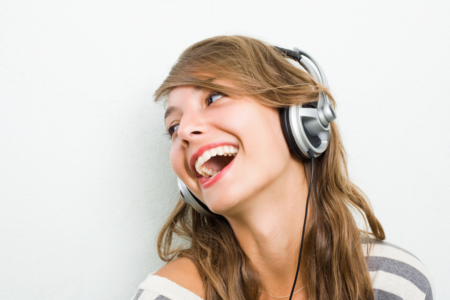 Portrait of a smiling young woman listening the music on ... |Woman Listening To Music