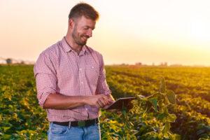 Agricultor com smartphone acessando as redes sociais e sites de empresas de comodities vendo a cotação de sementes, soja, milho, algodão, ração para gado, defensivos, pulverização e colheitadeiras para planejamento de plantio.