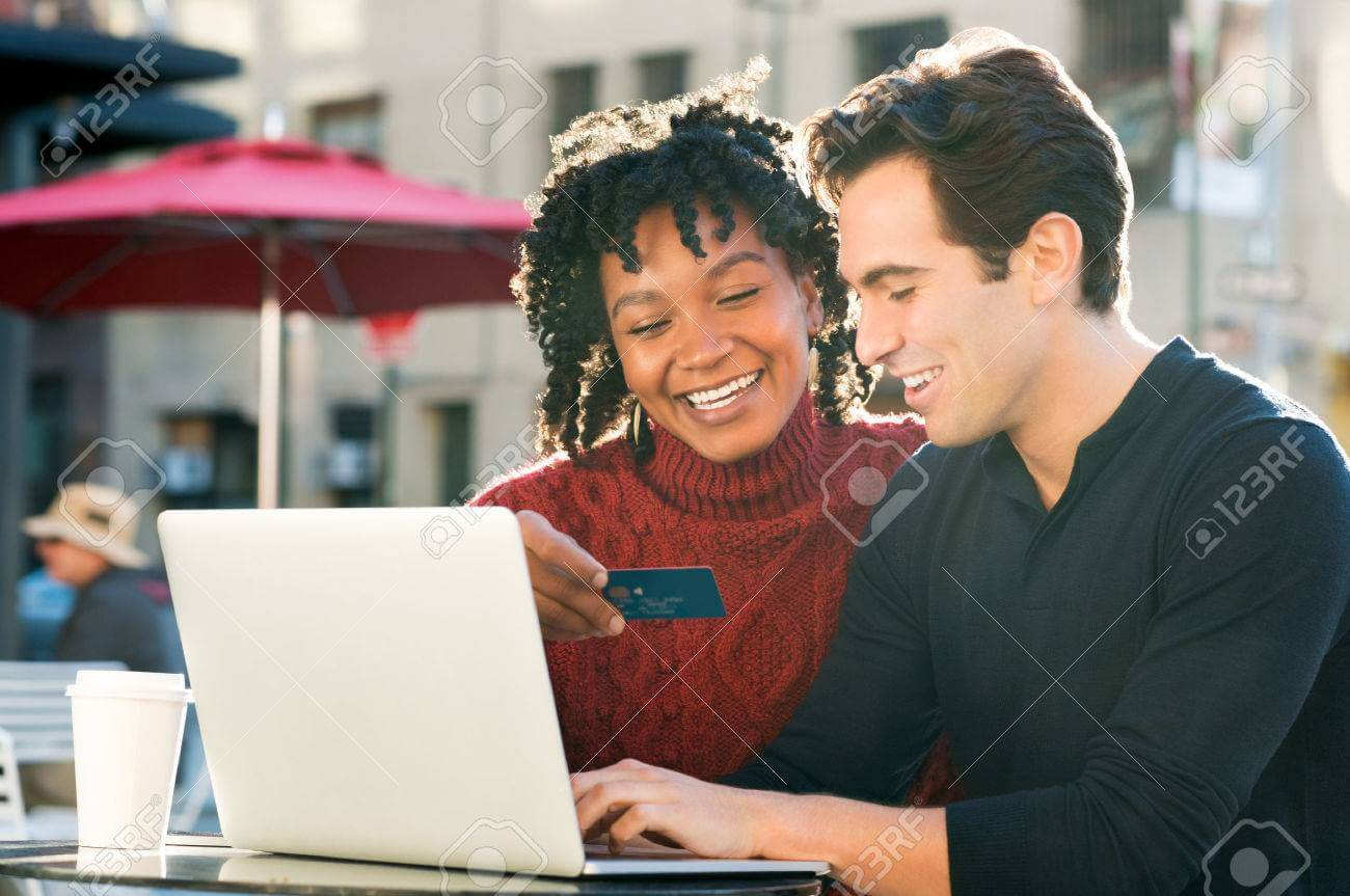 50076622-beautiful-young-loving-couple-shopping-online-together-while-woman-holding-credit-card-and-smiling-p