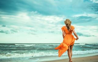 Woman on beach with orange dress