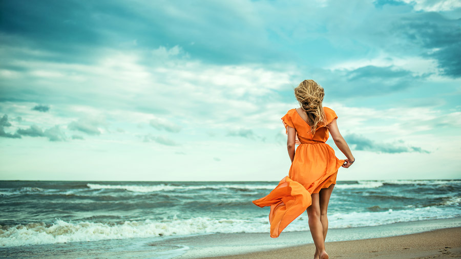 Woman on beach with orange dress