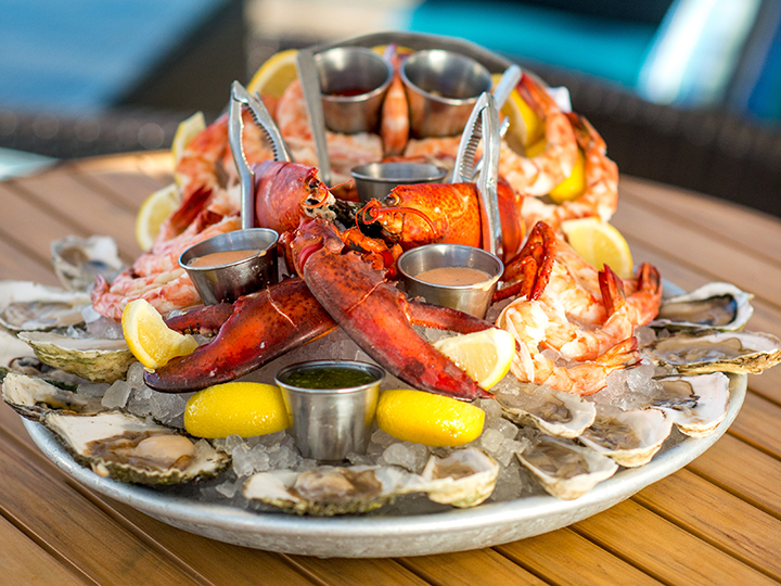 A platter of lobster, shrimp and oysters on a bed of ice with lemon wedges and cups of dipping sauce